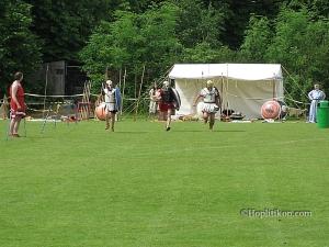 Σύγχρονη αναπαράσταση «βαρέας οπλιτοδρομίας». Από αριστερά προς τα δεξιά διακρίνονται τα εμβλήματα της Φωκίδας, των ιππέων της Κορίνθου και των μισθοφόρων ίδιας πόλης. Διεθνές αρχαιοελληνικό φεστιβάλ του Watford –Ιούνιος 2006 Από αρχείο του συγγραφέα.